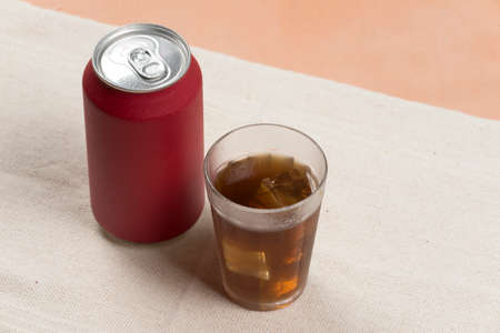 red soda can with a glass filled with ice Imagens