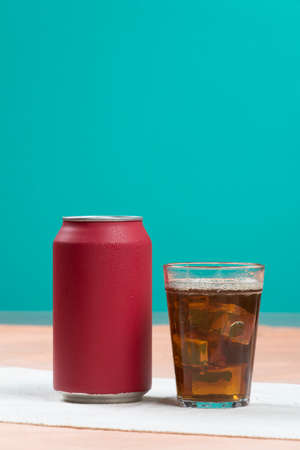 red soda can with a glass filled with ice