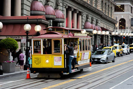San Francisco, CA, USA - june 01, 2019: cable car on the citys slope with passengers in the stirrups