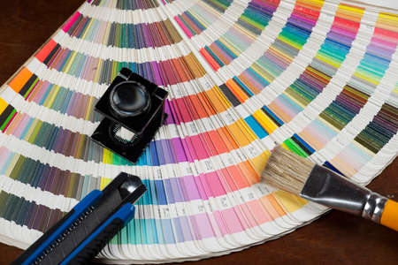 printed color swatch with a magnifying glass, cutter and paint brush