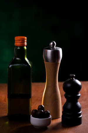salt shaker, pepper, bottle of olive oil over wooden table