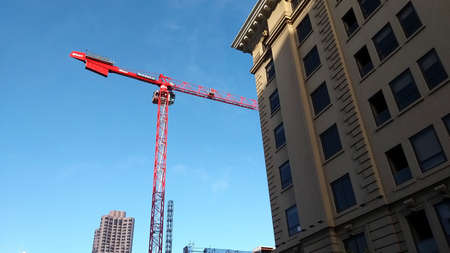San Francisco, USA - june circa, 2019: facade of old buildings during the day with a red crane at background Editorial