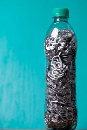 aluminum pull tabs inside plastic bottle to recicle Imagens