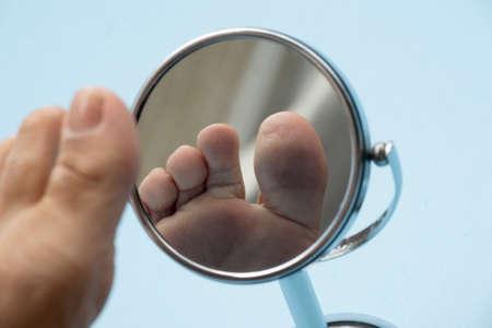 Personne regardant la plante du pied dans un miroir, pour vérifier s'il n'y a pas de pied diabétique, comme d'éventuelles plaies