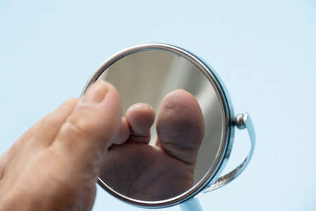 Person looking at the sole of the foot in a mirror, to check if there is no diabetic foot, as possible sores