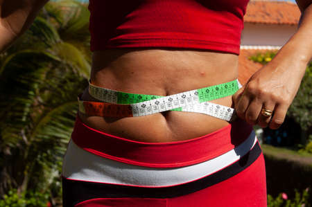 Slim woman measuring her waist to see if it is above ideal