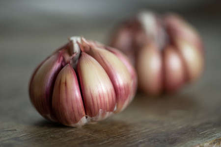 head of garlic on rustic wood lit by the sun