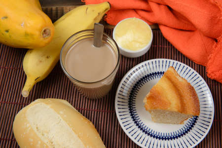 typical brazilian small breakfast, with cup of coffee with milk bread, cake and fruits