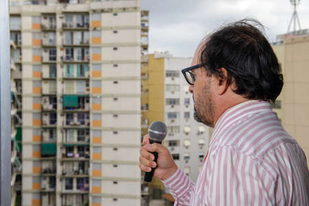 middle-aged man speaking into the microphone in a public place, with buildings in the background