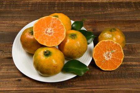 Fresh mandarin oranges fruit or tangerines in wooden table