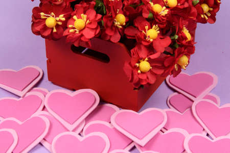 red box with flowers next to a heart and lilas background