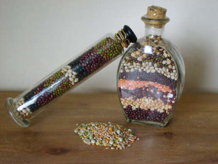 pulses: Two bottles of mixed dried pulses, one angled, and small pile of pulses Stock Photo