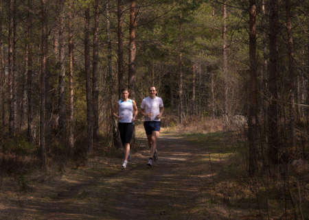 Young, caucasian couple running on an S-shaped trail in a beautiful forest setting photo
