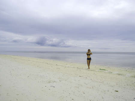 pinay: Filipina taking photos on a white sand beach