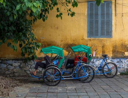 vietnamese men taking a nap on their bike in the street during work