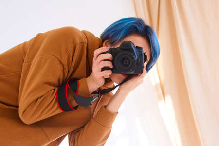 hipster girl holding camera and taking photo. closeup of hand of young woman with professional camera in studio. world photography day concept Zdjęcie Seryjne