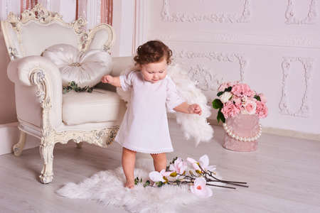 Little boy 1 year old like angel smile. international children's day. Toddler boy in angel wings in baroque style interior room.