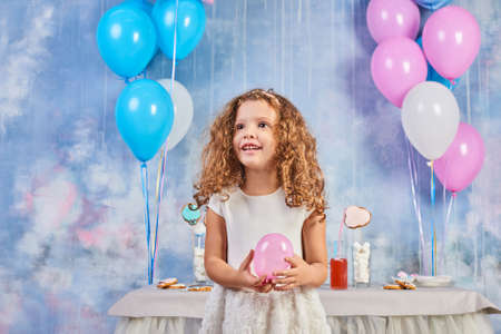 Children's funny birthday party in decorated room. Happy little girl celebrate International Children's Day. Funny child play at home