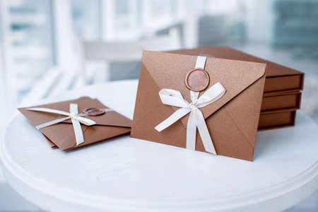 Gift Certificate, gift voucher or discount. close-up photo of bronze invitation envelope with a ribbon and wax seal, a gift certificate, a card, a wedding invitation card