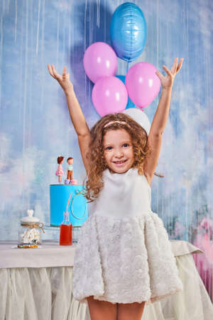 Children's funny birthday party in decorated room with balloons. Happy little girl celebrate International Children's Day. Funny child play at home Foto de archivo