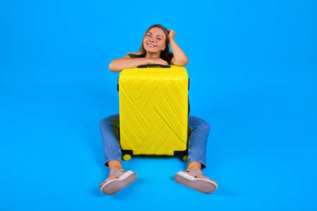 happy woman sit with yellow baggage on blue background. Concept girl dream about vacation Banco de Imagens