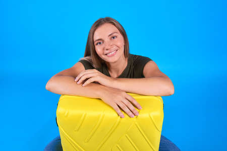 happy blonde woman sit with yellow suitcase on blue background. Concept caucasian girl dream about vacation Reklamní fotografie