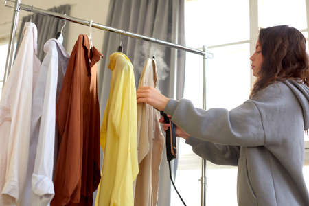 Girl steams clothes on hanger. Woman with steamer cleaning clothes in dry-cleaning salon Reklamní fotografie