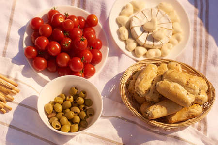 summer outdoor picnic with cherry, rollini, cheese, olives