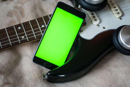 stratocaster: Smartphone with green screen on an Electric Guitars guitar