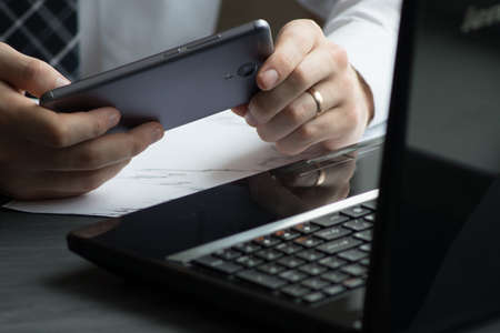 e commerce: Business man drinking coffee and using laptop computer and mobile smart phone at home, young man browsing internet on phone, e commerce or online working from home, IOT internet of things concept.