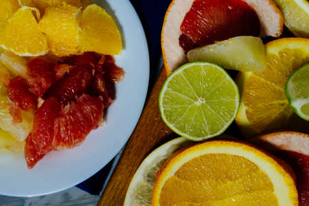 Various citrus fruit cut into slices orange, lemon, lime, grapefruit, pomelo. Spread out on a wooden board on a vintage background of natural wood texturing.