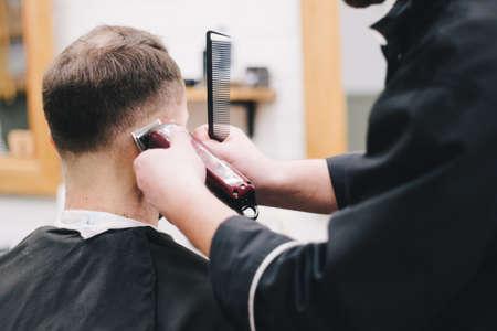 Barber cuts the client mac Haircut men Barbershop. Mens Hairdressers; barbers.