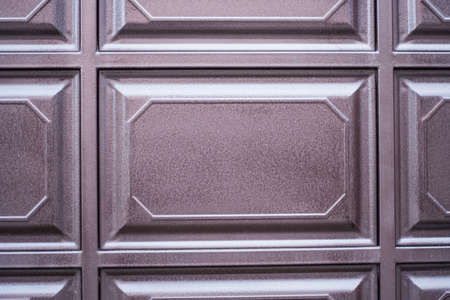 elegantly: Close view of an elegantly carved light brown wooden door with square pattern and an octagonal door knob on the left side.