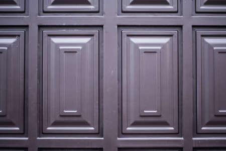 door knob: Close view of an elegantly carved light brown wooden door with square pattern and an octagonal door knob on the left side.