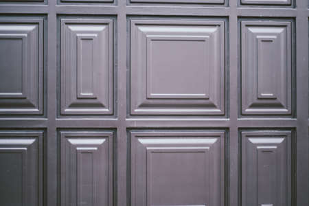 Close view of an elegantly carved light brown wooden door with square pattern and an octagonal door knob on the left side.