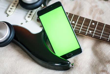Smartphone with green screen on an acoustic guitar