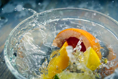tropical fruits citrus fall deeply under water with a big splash