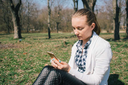 Beautiful young European girl sits on the grass in the park and uses a smartphone, concepts of using gadgets in a natural environment in the fresh air