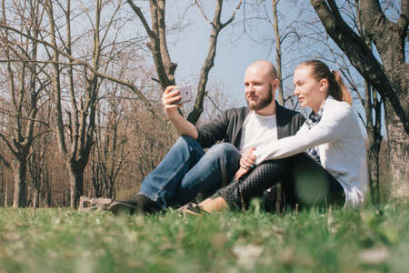 A young hippy guy and a pretty girl doing selfie sitting on the grass in the park and using a smartphone, concepts of using gadgets in a natural environment in the fresh air Stock Photo