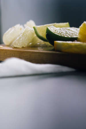 stack of citrus fruits slices. Oranges and lemons limes, grapefruit, pomelo. On wooden table Stock Photo