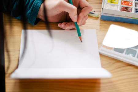 Cute little girl drawing. Elementary age. Stock Photo