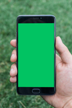 hand of man holding mobile smart phone with chroma key green screen on gren background Stock Photo
