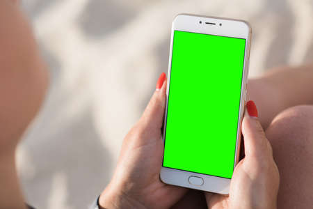Beautiful girl holding a smartphone in the hands of a green screen green screen, hand of man holding mobile smart phone with chroma key green screen on white background, new technology concept Stock Photo