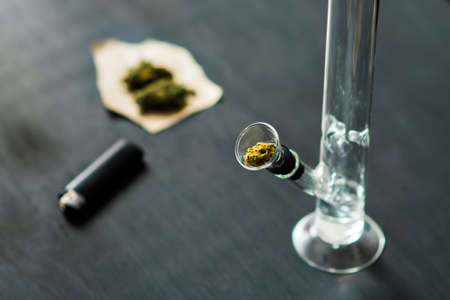 Bong and marijuana, cannabis thc flower Sativa and Indica Close up on a black background. lifestyle Concepts the legalization of marijuana in the world and the United States. Banco de Imagens - 90799439