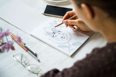 A girl is painting with pencils Husky on a white sheet Standard-Bild