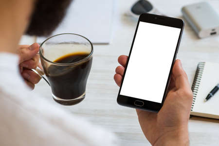 The man uses a smartphone with a white screen for the mock up Drinks coffee reading news. Concepts of using mobile devices, demos of the site in the mobile version medical use THC and CBD