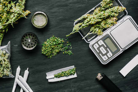 Cones of marijuana flowers on scales, grinder and shredded cannabis joint and a packet of weed on a black wood