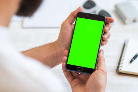 The man uses a smartphone with green screen for chroma key compositing. Concepts of using mobile devices, demos of the site