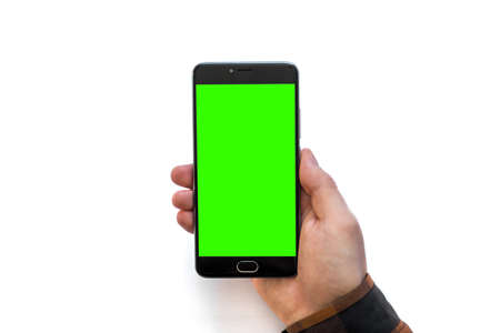 Hand holding black smartphone with green screen for chroma key compositing on white background Stock Photo