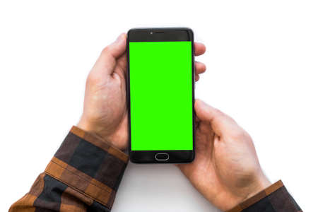 Hand holding black smartphone with green screen for chroma key compositing isolated on white Stock Photo - 95064350